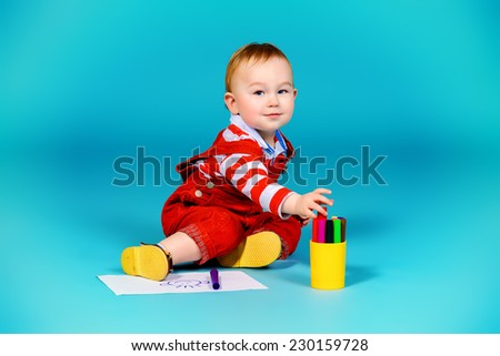 Cute baby boy playing with felt pens on a floor. Childhood. - stock photo