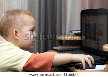 Cute baby boy playing with laptop