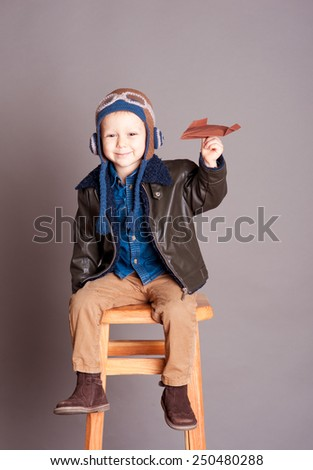 Cute baby boy playing with origami plane in room over gray. Sitting on wooden chair. Wearing stylish leather jacket. Smiling kid. Childhood.