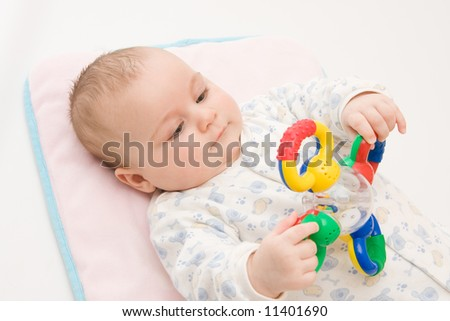 cute baby boy playing with rattle on light background - stock photo