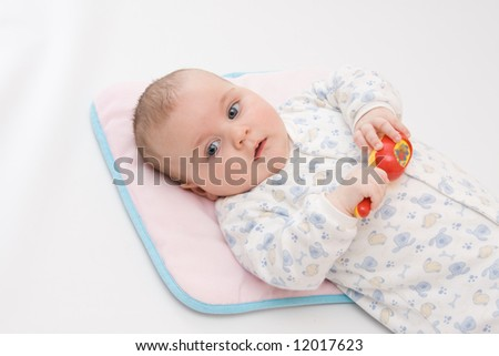cute baby boy playing with rattle on light background