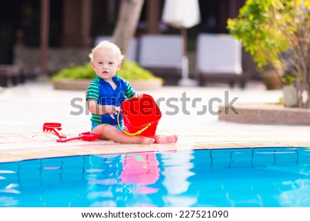 Cute baby boy playing with red toy bucket at swimming pool in a tropical resort - stock photo