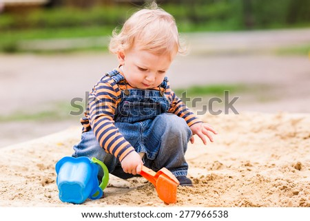 Cute baby boy playing with sand in a sandbox