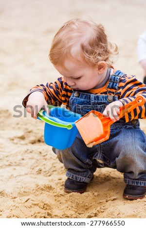 Cute baby boy playing with sand in a sandbox - stock photo