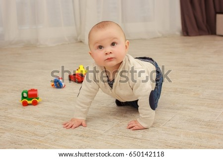 cute baby boy playing with toys in living room at home