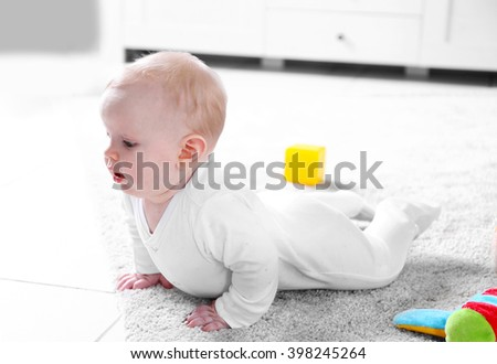 Cute baby boy playing with toys on white carpet at home - stock photo