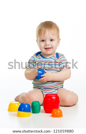 Cute baby boy playing with toys while sitting on floor, isolated over white - stock photo
