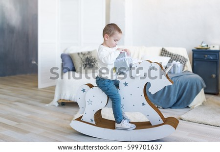 Cute baby boy riding wooden traditional rocking horse toy in white bedroom. Child playing in nursery room. Gift box for toddler kid.