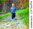 cute baby boy running beautiful autumn footpath - stock photo