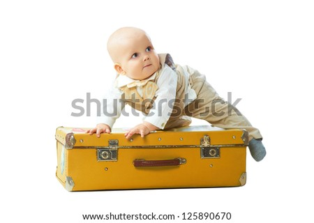 Cute baby boy sit on the big vintage suitcase isolated on white background - stock photo