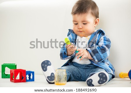 Cute baby boy sitting at home and playing with spoon