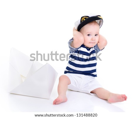 cute baby boy sitting in captain cap with ship of paper - sailor in future, over white background - stock photo