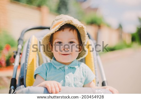 cute baby boy sitting in stroller