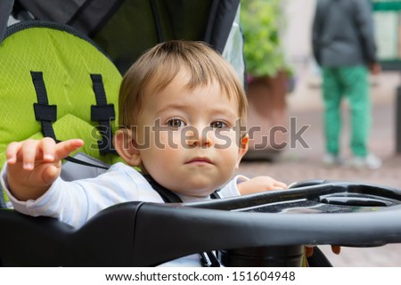 Cute Baby boy sitting in stroller outdoors - stock photo
