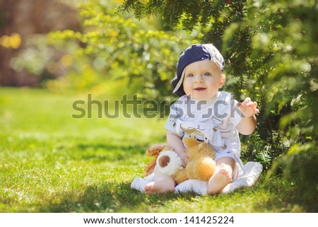 Cute baby boy sitting in summer park on the grass. Outdoor portrait - stock photo