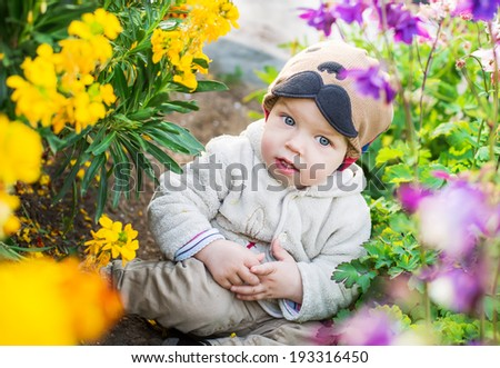 cute baby boy sitting in the flowers in the spring time - stock photo