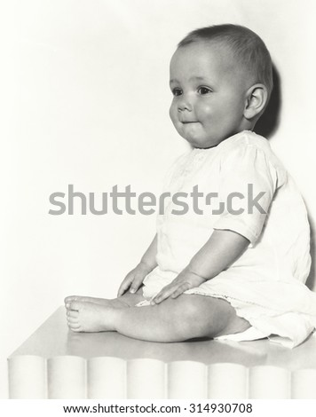 Cute baby boy sitting on table - stock photo