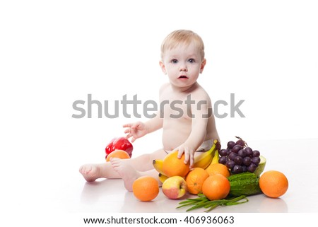 Cute baby boy sitting with fruits and vegetables isolated on white background