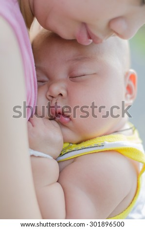 Cute baby boy sleeping on his mother. - stock photo