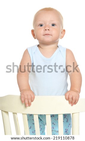 Cute baby boy smiling and standing on the chair - stock photo