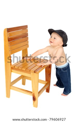 Cute baby boy standing up against a wooden chair