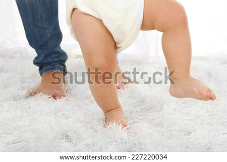 Cute baby boy taking first steps with mother in room - stock photo