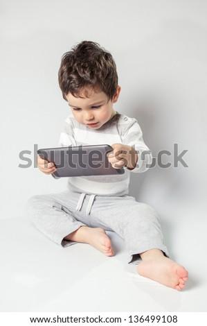 Cute baby boy using digital tablet. - stock photo