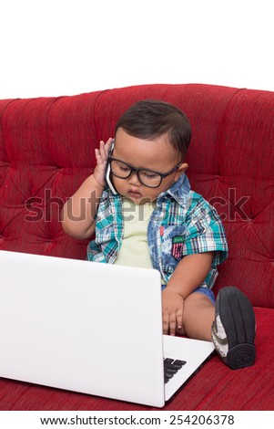 Cute baby boy using white laptop and cellular phone for manage his online business at red sofa - stock photo