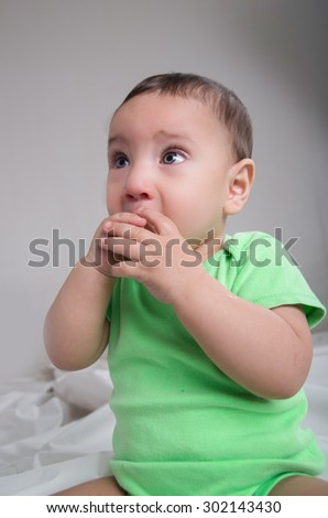 cute baby boy wearing green clothing sitting in front of camera covering mouth with hands and staring to the side. - stock photo