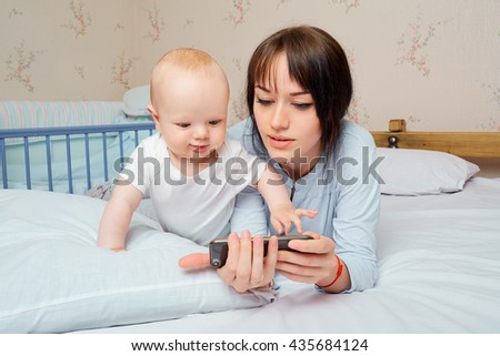 Cute baby boy with a beautiful brunette mother on the bed in the room, watching with enthusiasm to your phone. Home furnishings. A happy family. - stock photo