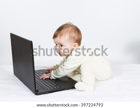 Cute baby boy with black laptop on white carpet