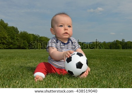 cute baby boy with blue eyes playing on grass with ball, photo