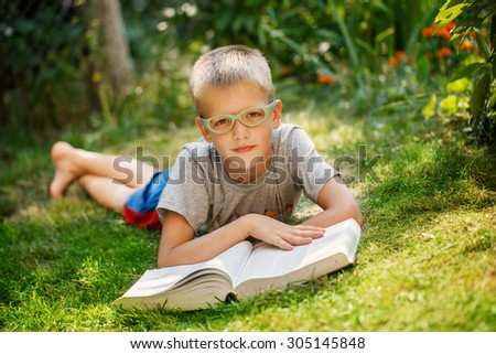 Cute baby boy with glasses lying on green grass, reading the book in summer day. - stock photo