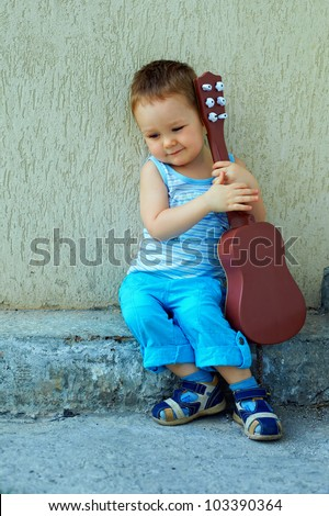 cute baby boy with guitar sitting against the concrete wall