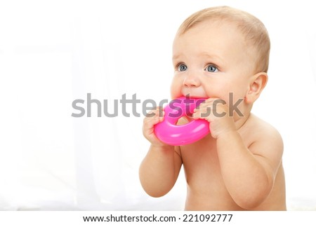 Cute baby boy with plastic ring on light background