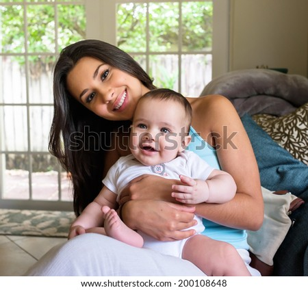 Cute baby boy with pretty young woman in a home setting. - stock photo