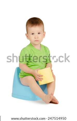 Cute baby boy with toilet paper sitting on a blue potty isolated on white background