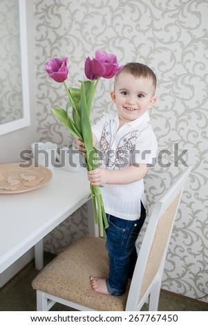 Cute baby boy with tulip flowers indoor portrait - stock photo