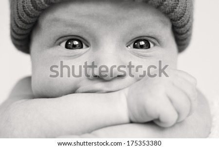 Cute baby boy with wide eyes funny sucks hand closeup ( black-white ) - stock photo