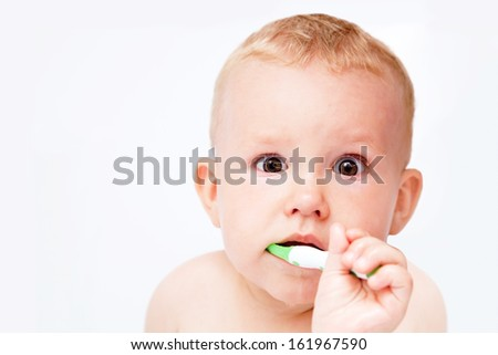 Cute baby brushing his teeth and looking at the camera on white background