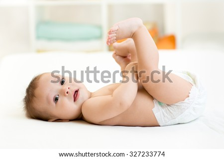 cute baby child little boy lying on his back and holding legs - stock photo
