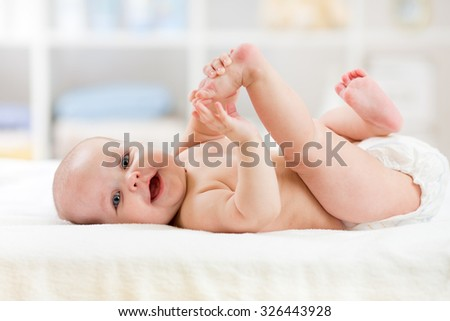 cute baby child lying on white sheet and holding his legs - stock photo