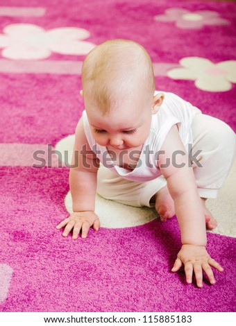 Cute baby crawling on soft pink carpet