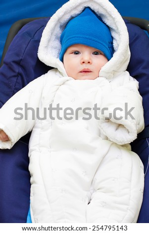 Cute baby dressed in warm fluffy winter clothes.
