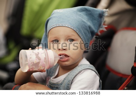 cute baby drinks juice sitting in baby carriage - stock photo