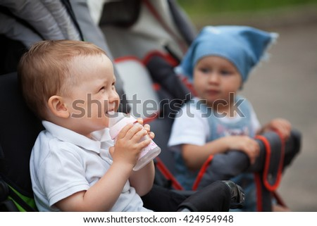 cute baby drinks juice sitting in baby carriage