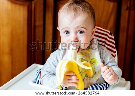 Cute baby eating banana - stock photo