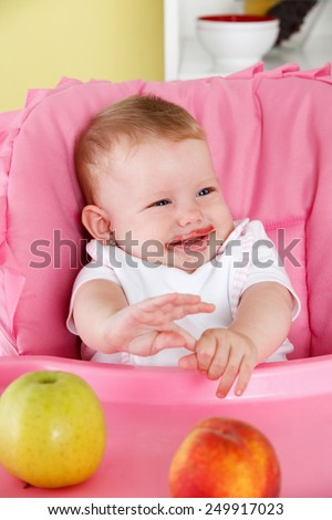 Cute baby eating in the high chair