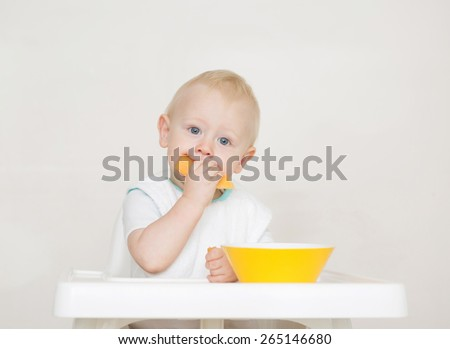 Cute baby eating in white high chair against white background with a yellow bowl.   - stock photo