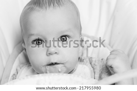 Cute baby eating porridge on a white background  ( black and white ) - stock photo